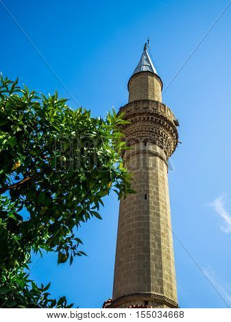 mosque minaret and trees blue sky background