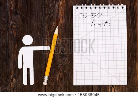 Paper man holding pencil and blank notebook with todo list wooden background. Abstract conceptual image