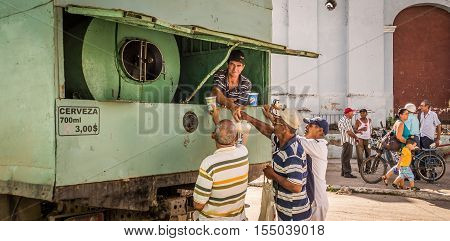 Sancti Spiritus, Cuba on January 1, 2016: Cuban men buying beer from a truck to celebrate New Year. Homebrew beer is popular in Cuba and very cheap, 700ml costs only 3 CUP, ca. 0, 12 USD