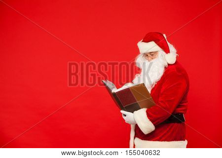 Santa Claus reads old book, on a red background. Christmas.