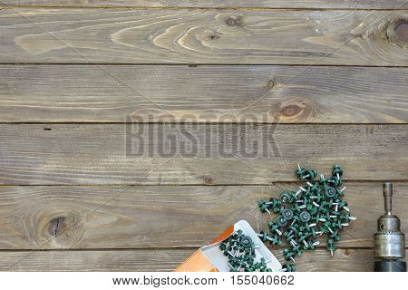 Roofing screws and a drill on a wooden table. The view from the top. Place for advertising and labels.Roofer, roofing work.