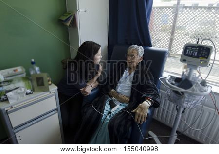 Social worker visit sick old male patient in hospital.