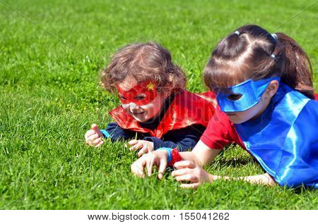 Superhero sisters lay on green grass play outdoors. concept photo of Super hero girl power play pretend childhood imagination. Real people