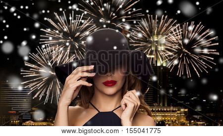 people, luxury, christmas, new year and winter holidays concept - beautiful woman in black hat over night singapore city and firework background with snow