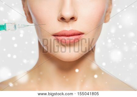 people, cosmetology, plastic surgery, anti-aging and beauty concept - close up of beautiful young woman face and syringe making injection over gray background and snow
