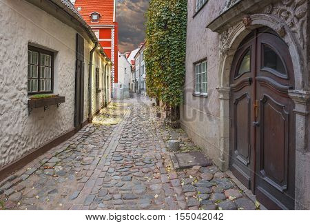 Narrow street in old Riga - the capital of Latvia and famous tourist city in Baltic region where everyone can feel unforgettable atmosphere of Middle Ages and unique Gothic architecture