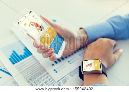 sport, fitness, technology, responsive design and people concept - close up of female hand holding smart phone and wearing watch with sports application on screen