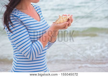 Young beautiful slim girl with brown hair standing on a seashore one windy morning and holding a seashell. Summer vacation