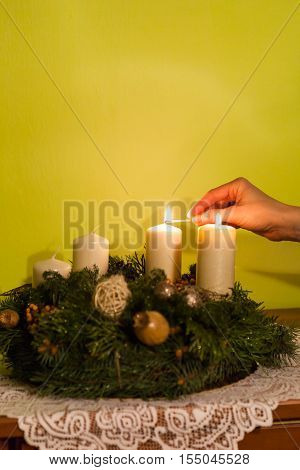 Woman hand lit the second advent wreath candle