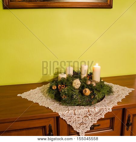 Advent wreath on rustic furniture with white tablecloth