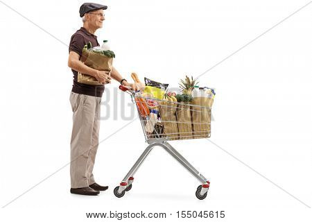Full length profile shot of a senior with a paper bag and a shopping cart filled with groceries waiting in line isolated on white background