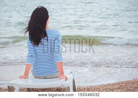 Young woman with brown hair sitting on a deck chair on the seashore one windy morning. Summer vacation