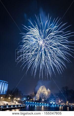 Spectacular fireworks over river at night on black background