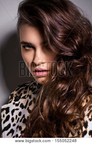 Girl in leopard blouse possing ia studio