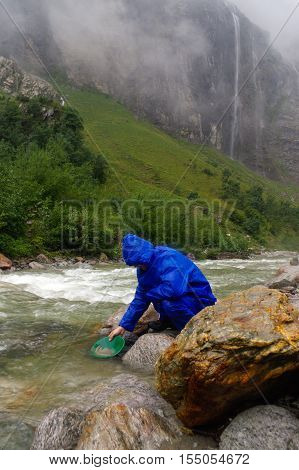 a man gold panning in a river with a sluice box during rain
