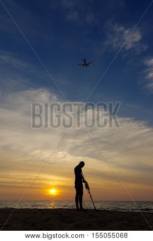 a treasure hunter with Metal detector on sunset on the beach with a plan in the sky