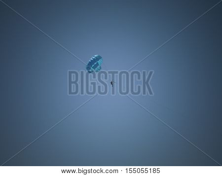 a man's blue parachute gliding in the blue sky