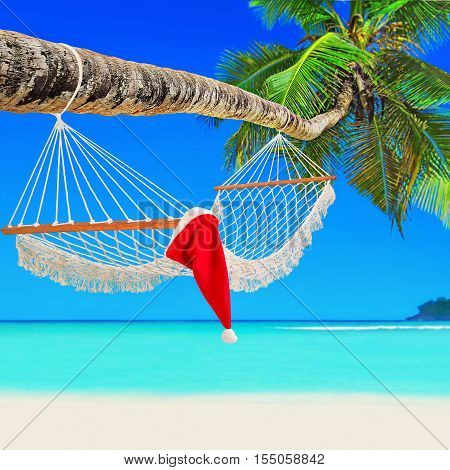 Santa Claus hat on wooden mesh hammock on perfect tropical white sandy coconut palm beach Baie Lazare Mahe island Seychelles Indian Ocean
