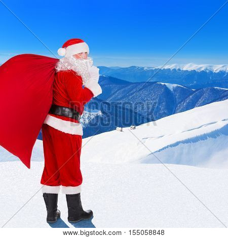 Santa Claus with big Christmas bag full of gifts against village in snowy winter mountains forest and blue sky landscape coming for wish children a happy New Year holiday