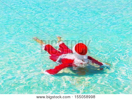 Santa Claus relax swimming in ocean turquoise azure transparent water Christmas and New Year holidays travel destinations in hot countries concept