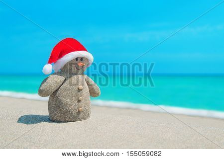Funny sandy Snowman in red Santa hat and orange carrot at sunny beach. Happy New Year and Christmas holidays concept for travel in tropical countries and resorts