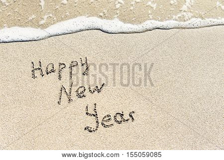 Happy New Year caption on white tropical sea beach sand with wave foam - Christmas holidays congratulation greeting card concept