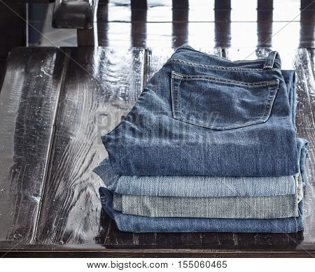 Stack of denim jeans texture or denim jeans background on wood table. Old grunge vintage denim jeans. Stitched texture denim jeans background of fashion jeans design.