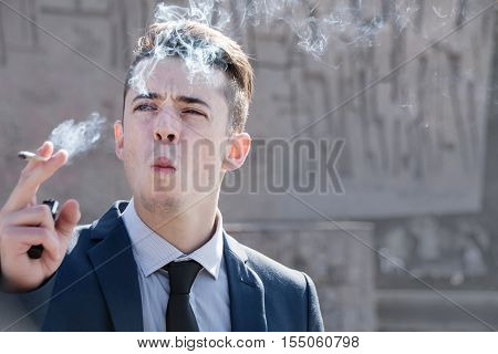 Young Business Man Smoking In The Street