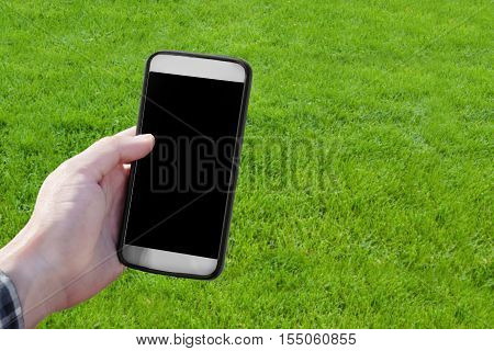 Hand Holding Smartphone Over Green Grass Background