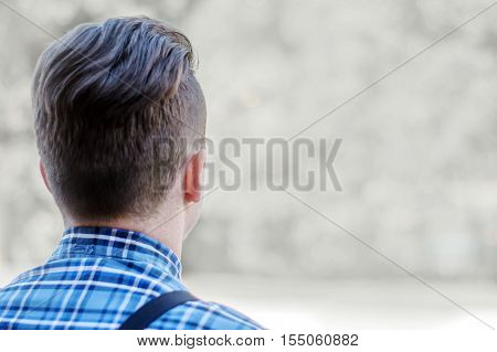 Close shot of man's head staring at neutral background