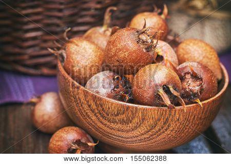 Common medlar fruit (mispel) in wooden bowl