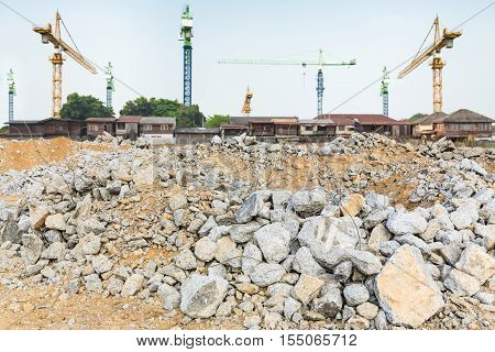 pieces of concrete and brick rubble debris on construction site with cranes and village in the background