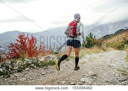 rear view of athlete runner in backpack for running and nordic walking stick running on a mountain marathon
