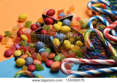 Mix of colorful dragee with raisins or peanuts inside marmalade or jelly candies striped caramel candies and silver star on colorful background