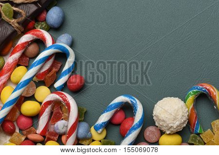 Dark green textured background with mix of colorful dragee with raisins or peanuts inside marmalade or jelly candies striped caramel candies coconut candy and chocolate bar with thread copy space