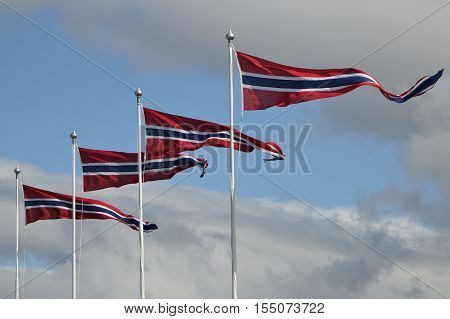 Four pennants fluttering in a wind against a cloudy sky in Norway