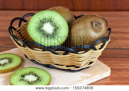 fresh kiwi fruits and slices of kiwi fruit in basket on wood