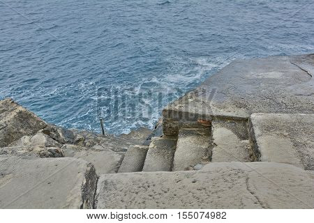 Steps cut into stone leading down into the Adriatic Sea by Dubrovnik's walls