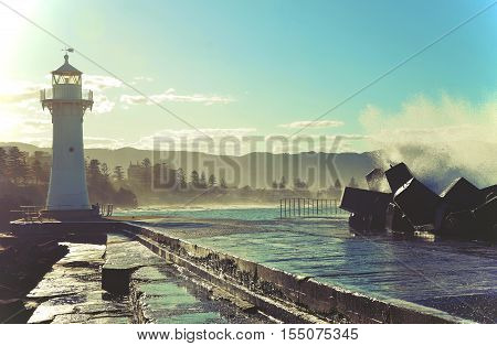 Big waves breaking over Wollongong harbor breakwall and lighthouse, Wollongong, New South Wales, Australia