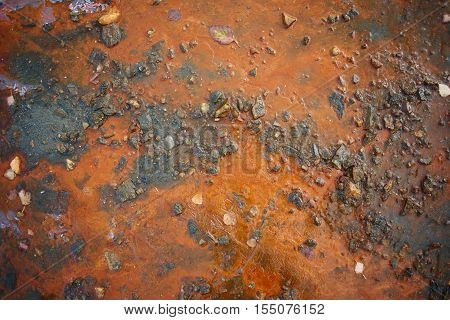 Orange precipitate on the banks of the river closeup