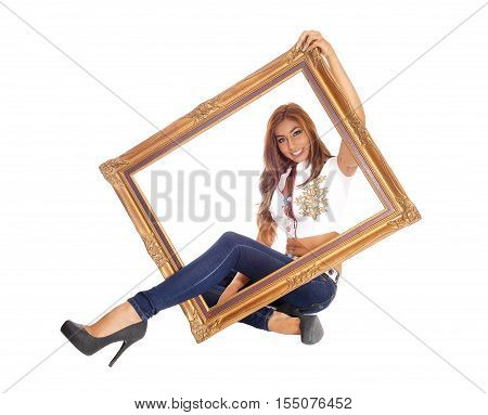 A beautiful young woman sitting in jeans with one leg trough a picture frame isolated for white background.