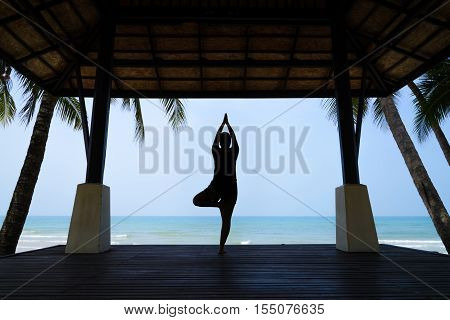 Silhouette Young Woman Practicing Yoga In Pavilion In Front Of The Beach