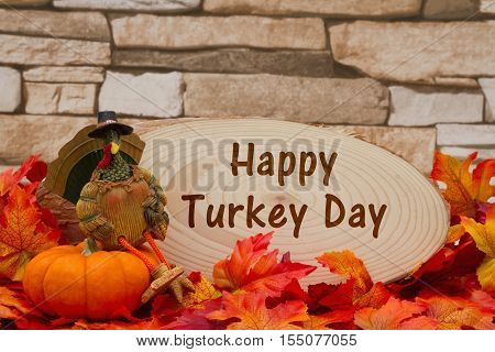 Happy Thanksgiving message Some fall leaves turkey on a pumpkin and wood plaque on weathered brick with text Happy Turkey Day