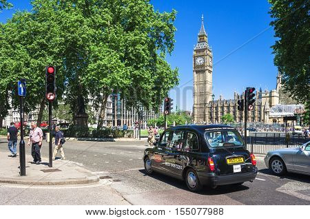 London UK - June 10 2006: Iconic black taxi cab in front of symbol of London Big Ben tower (Houses of Parliament). Hackney carriage (a cab black cab hack or London taxi) is a automobile for hire.