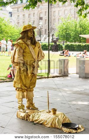 London UK - June 11 2006: City street performance of gold painted actor in suit of a king of 17 century. Living statues is the entertainment for passerby.