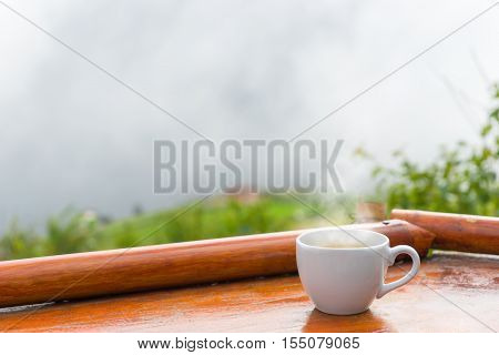A Cup Of Coffee Put On Old Wooden Table With View Of Morning Fog