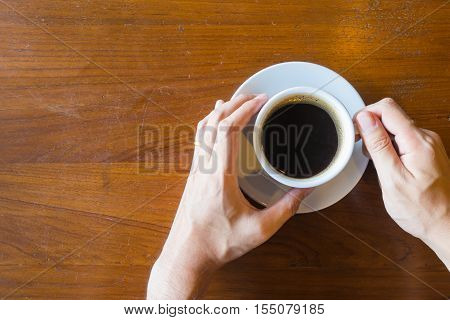 Top View Of Hand's Man Hold A Cup Of Hot Coffee On Old Wooden Table Background