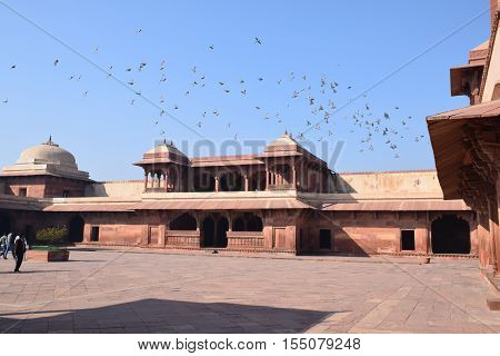 FATEHPUR SIKRI, UTTAR PRADESH, INDIA - FEBRUARY 05, 2016 - Old building and flying birds inside Fatehpur Sikri archaeological site