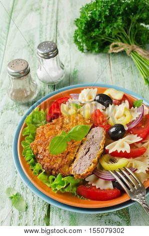 Cornflake crunchy pork cutlets served with pasta salad. Homemade cutlets on a wooden table in a rustic style