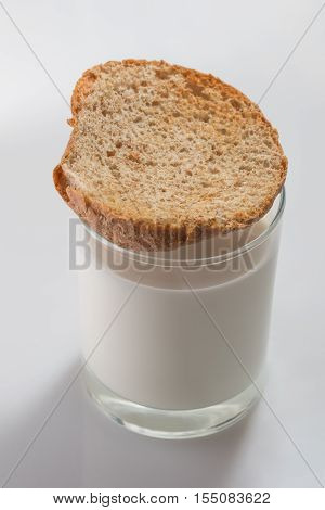Toasted bread on top of colorless glass full of cow milk on white background